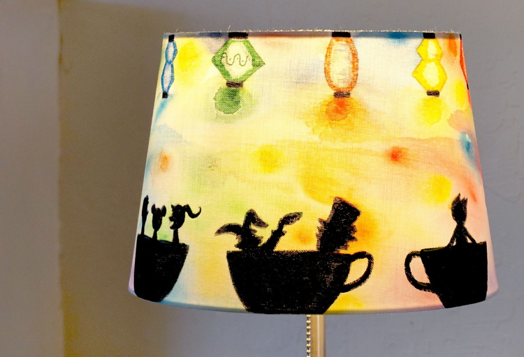Close up of a lampshade with people riding teacups