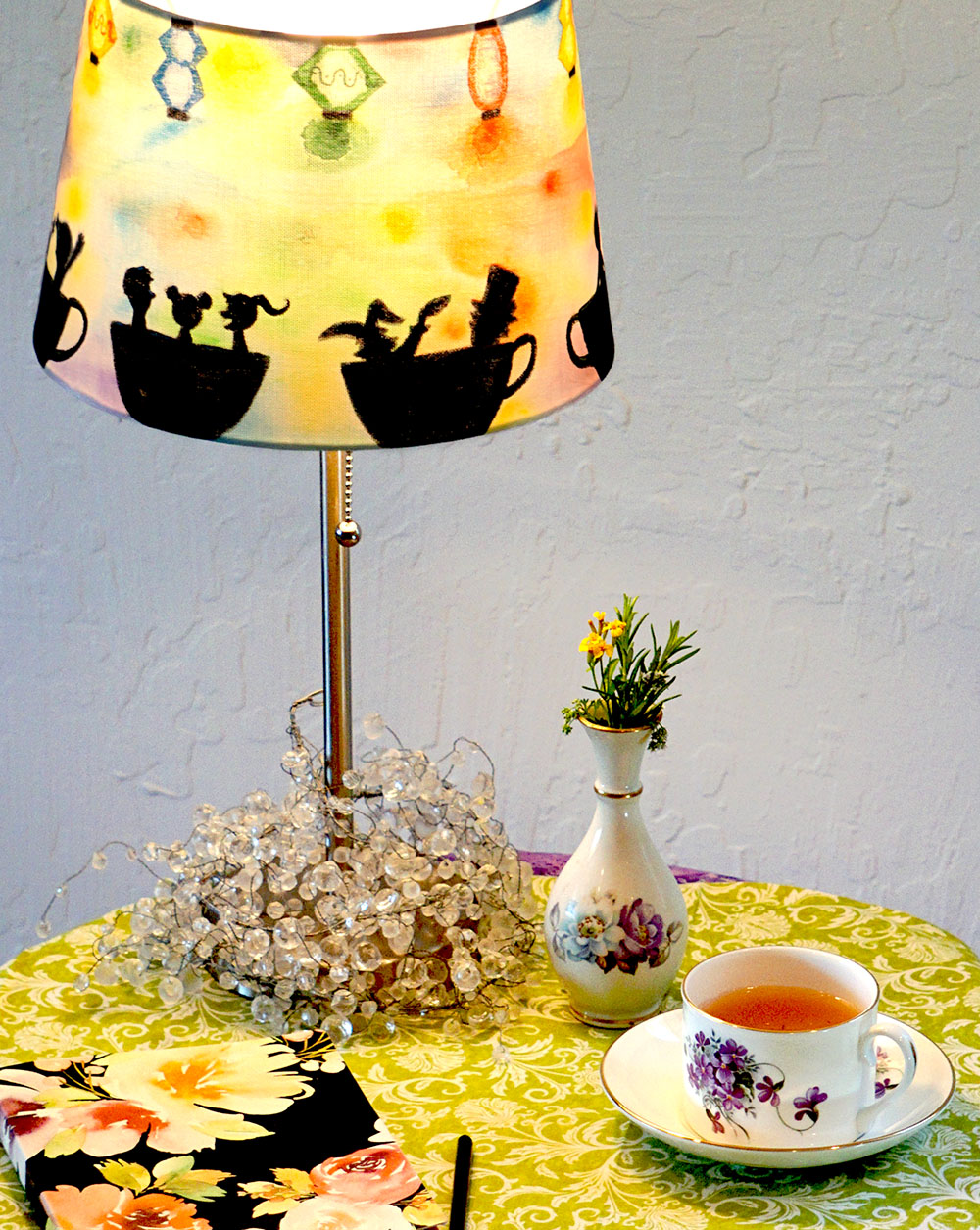 Lampshade with watercolor like background and people riding teacups lining the bottom.