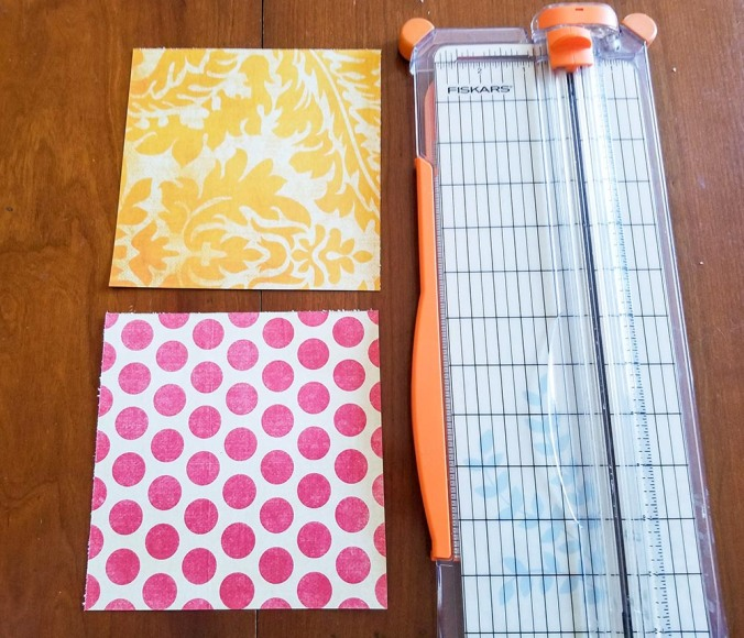 two different pieces of patterned scrapbook paper next to a paper cutter